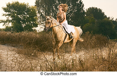 Young woman racing on horse (motion blur) - Attractive girl...