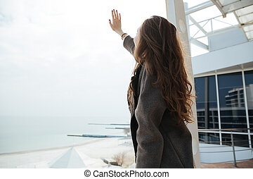 Young woman raising her hand