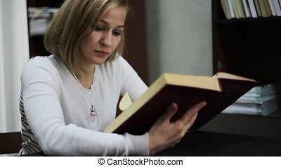 young woman reading a big book in library. bookshelves with books