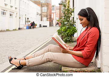 young woman reading a book and listening to music.