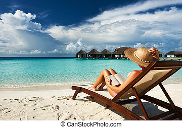 Young woman reading a book at beach - Young woman reading a...