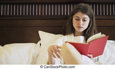 Young woman reading a book in bed, front view