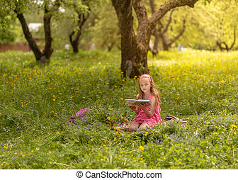 Young woman reading a book in the park