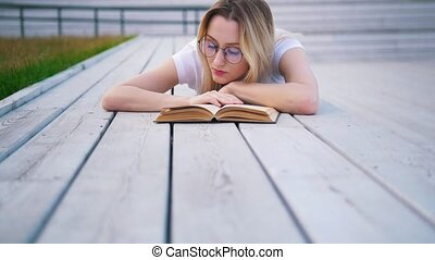Young woman reading a book lying outdoors in urban park