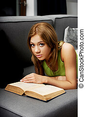 Young woman reading a book on sofa.