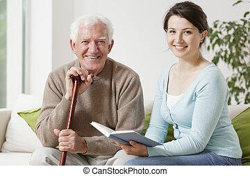 Young woman reading a book - Old man holding cane and young...