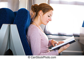 Young woman reading a book while on a train