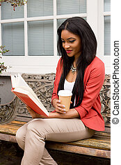 young woman reading a book with a coffee