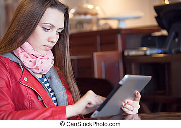 Young woman reading a digital tablet