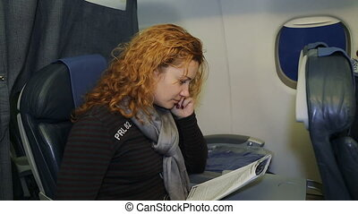Young woman reading a magazine in an airplane flying and smiling. Young woman in the interior of an airplane. Reading on board the aircraft.