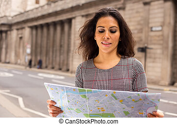 young woman reading a map in the city
