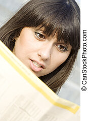 Young woman reading a newspaper outdoors