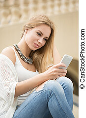 young woman reading a text message. on the street