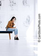 Young woman reading art guidebook - Young woman sitting on...