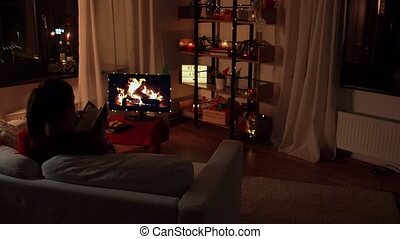 winter holidays, leisure and people concept - young woman reading book at cozy home decorated for christmas