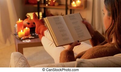 halloween, holidays and leisure concept - young woman reading book and resting her feet on table at cozy home