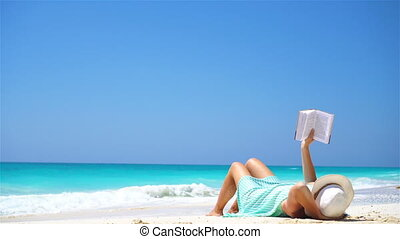 Young woman reading book during tropical white beach - Young...