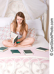 Young woman reading book in bed