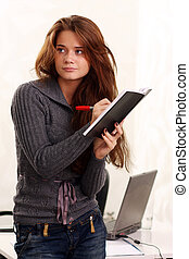 Young woman reading book in office