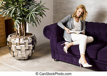 Young woman reading book on modern sofa