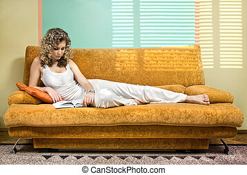 Young woman reading book on sofa at morning