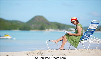 Young woman reading book on sunbeds during tropical white...