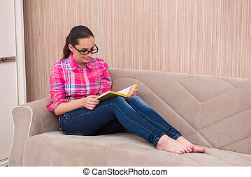 Young woman reading book on the sofa