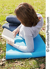 Young woman reading book side view