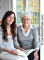 Young woman reading book to elderly woman