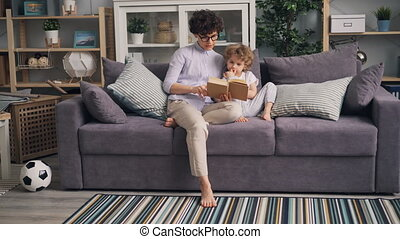 Young woman reading book to her son sitting on sofa in studio apartment together