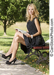 Young attractive blond woman reading book in park outdoor