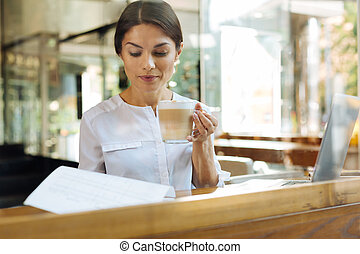 Young woman reading contract while drinking latte - Inspired...