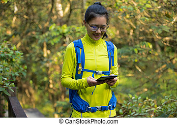 young woman reading ebook on park