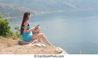 Young Woman Reading eBook - Young caucasian woman reads an...