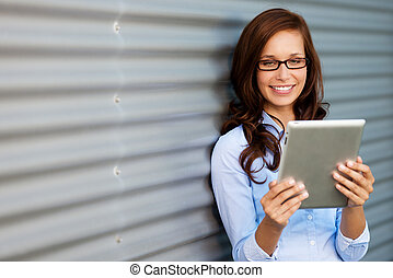 Young woman reading her tablet computer