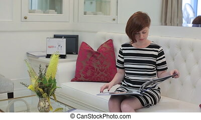 Young woman reading magazine in a luxury office