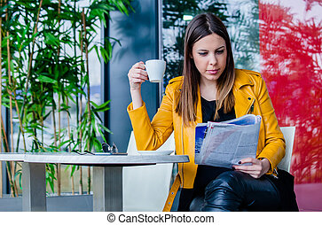 young woman reading magazine in cafe outdoor