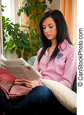 young woman reading news in a newspaper