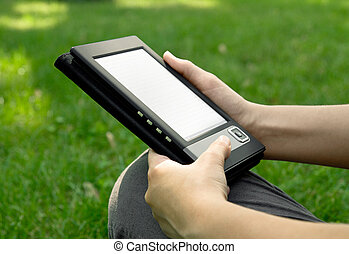 Young woman reads electronic book sitting on the grass.