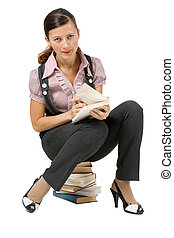 woman reading sitting on a pile of books