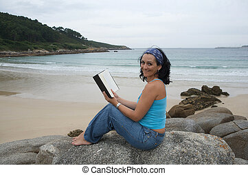 Young woman reading sitting on the beach