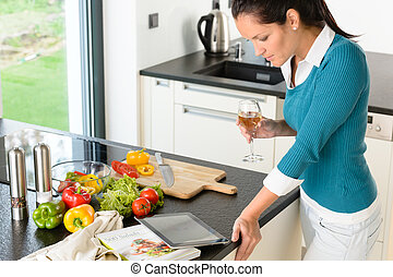 Young woman reading tablet recipe kitchen preparing food looking wine