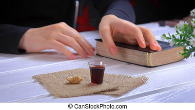 Young woman reading the Bible and taking communion - the wine and the bread symbols of Jesus Christ blood and body with Holy Bible. Focus on glass. Closeup dolly shot