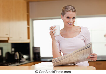 Young woman reading the news while having coffee