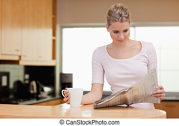 Young woman reading the news while having tea in her kitchen