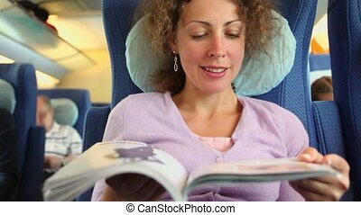 Young woman reads book when sit in chair at train coach