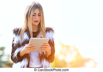 Young woman reads tablet standing