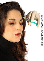 Young woman receives botox injection in her forehead -...