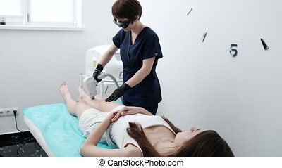 Young woman receives laser hair removal for legs at beauty salon.
