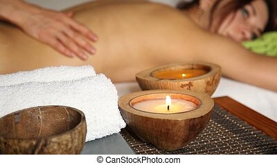 Young woman receiving a back massage in the spa salon. closeup hands of the masseur